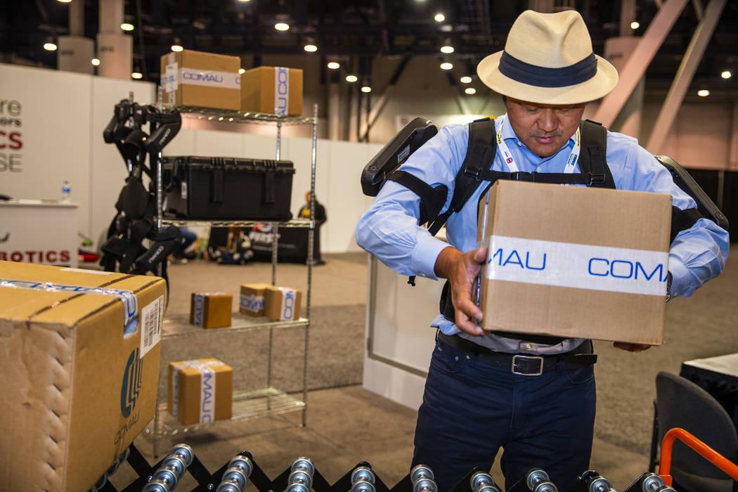 El asistente Toshiki Miyasaka levanta una caja con la ayuda de un aparato robótico MOS Exoskel ...