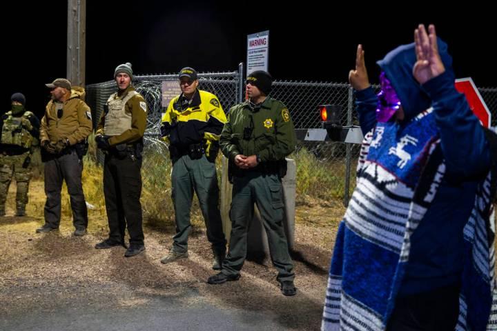 Un hombre disfrazado se encuentra cerca del personal de seguridad fuera de la puerta trasera de ...