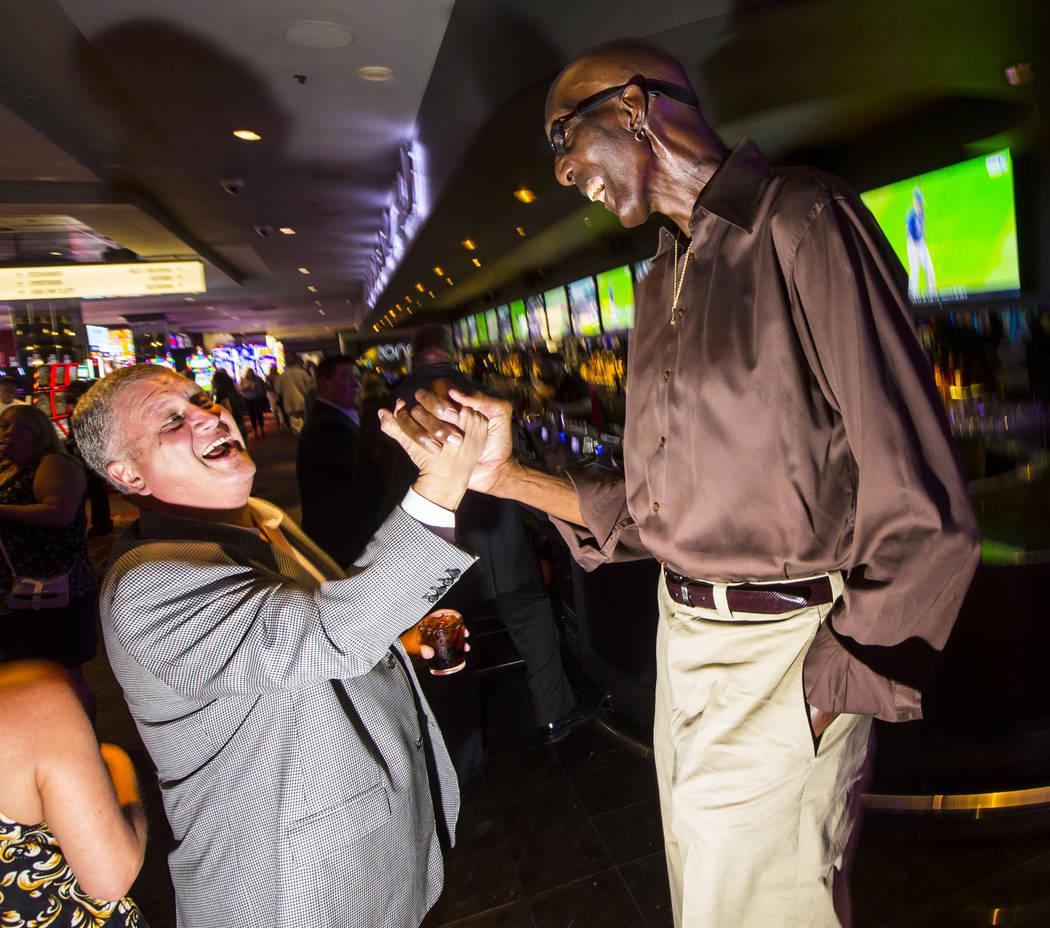 George Bell, que mide 7 pies y 8 pulgadas de alto, habla con Derek Stevens, dueño de The D Las ...