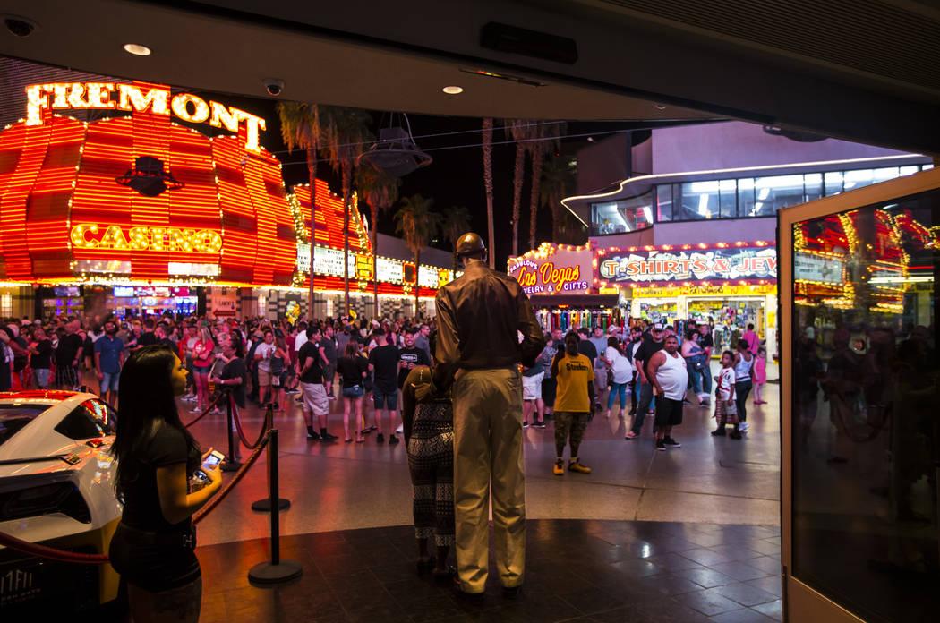 George Bell, que mide 7 pies y 8 pulgadas de alto, habla con los turistas mientras pasa el rato ...