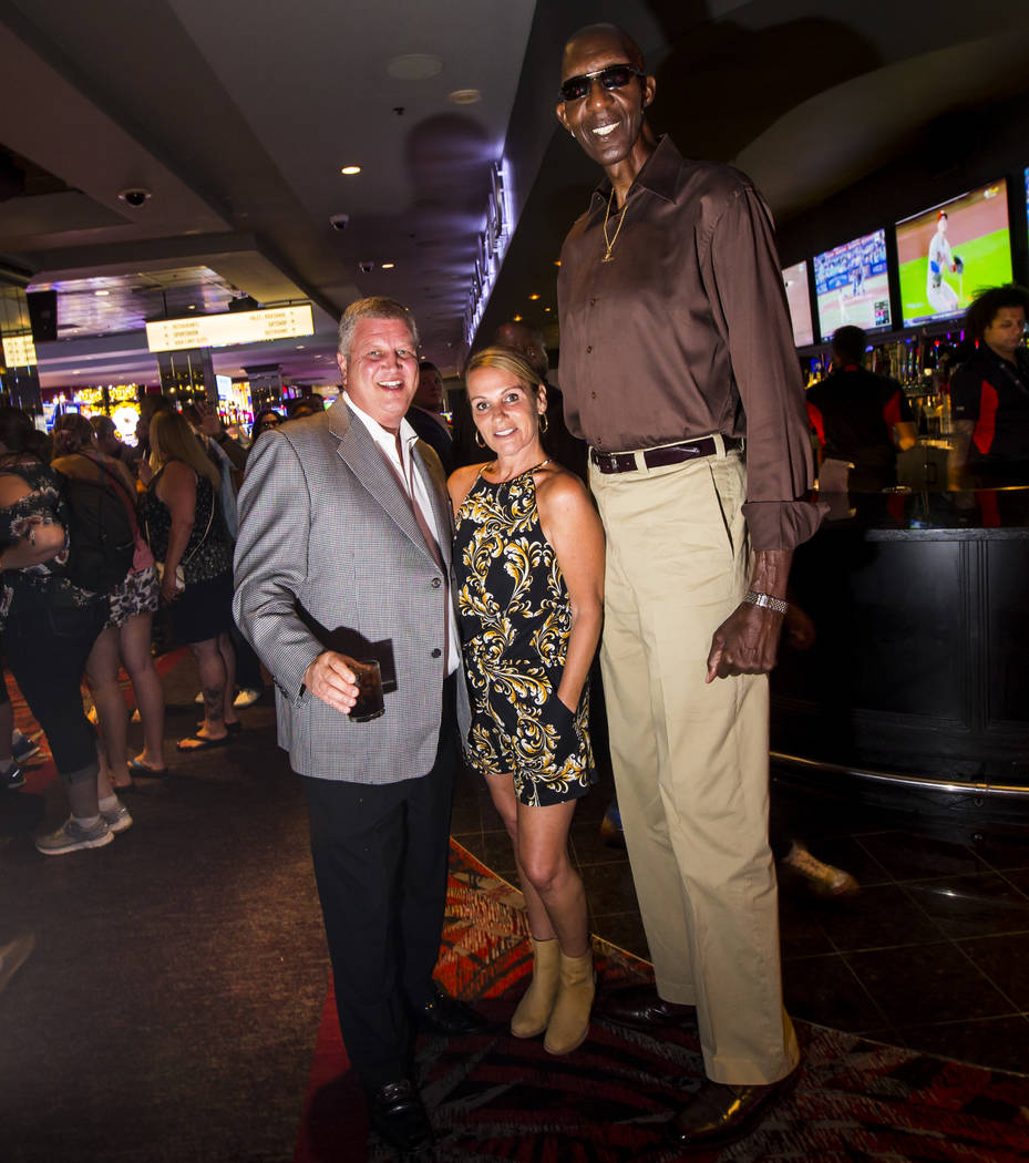 George Bell, que mide 7 pies y 8 pulgadas de alto, posa con turistas en el Longbar en The D Las ...