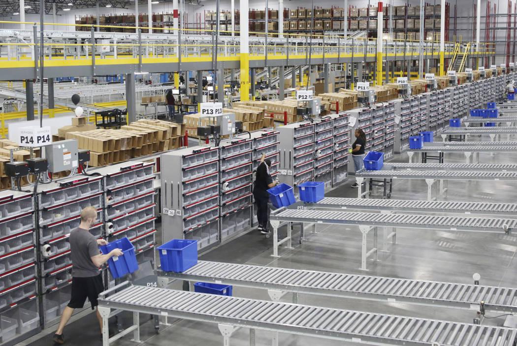 Los asistentes asociados del almacén clasifican el producto en el Centro de Distribución Seph ...