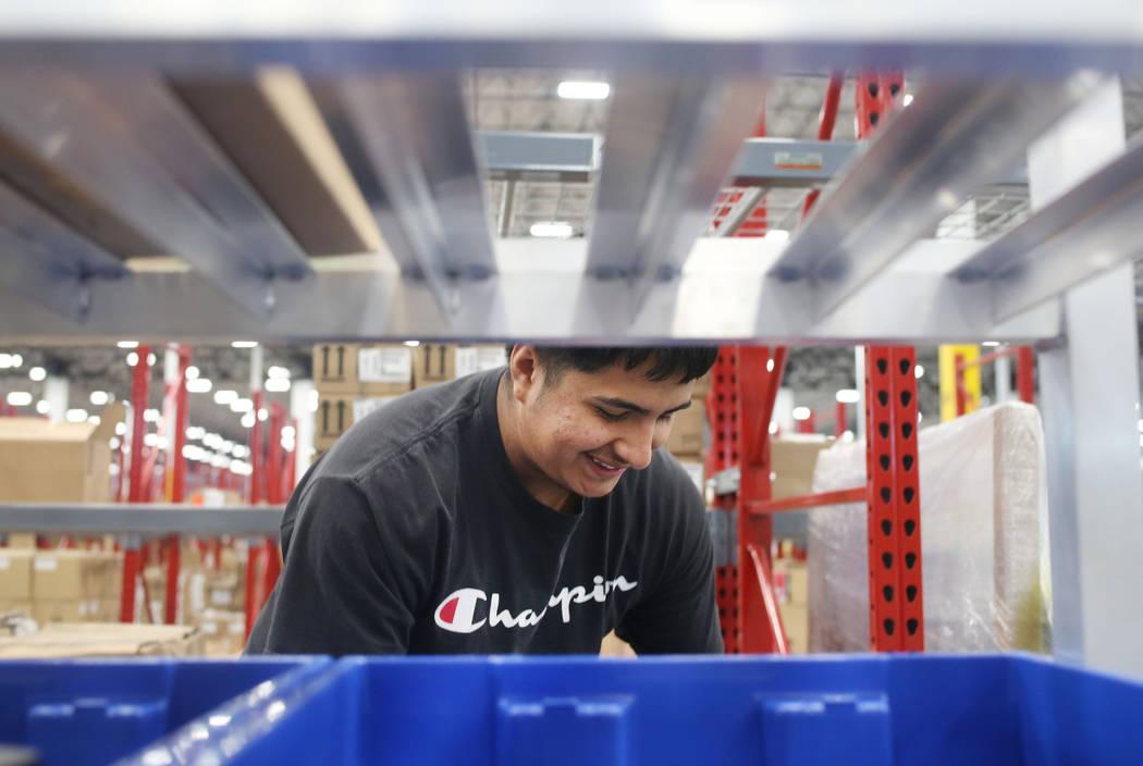 El asistente de almacén Enrique Román, clasifica productos en el Centro de Distribución Seph ...
