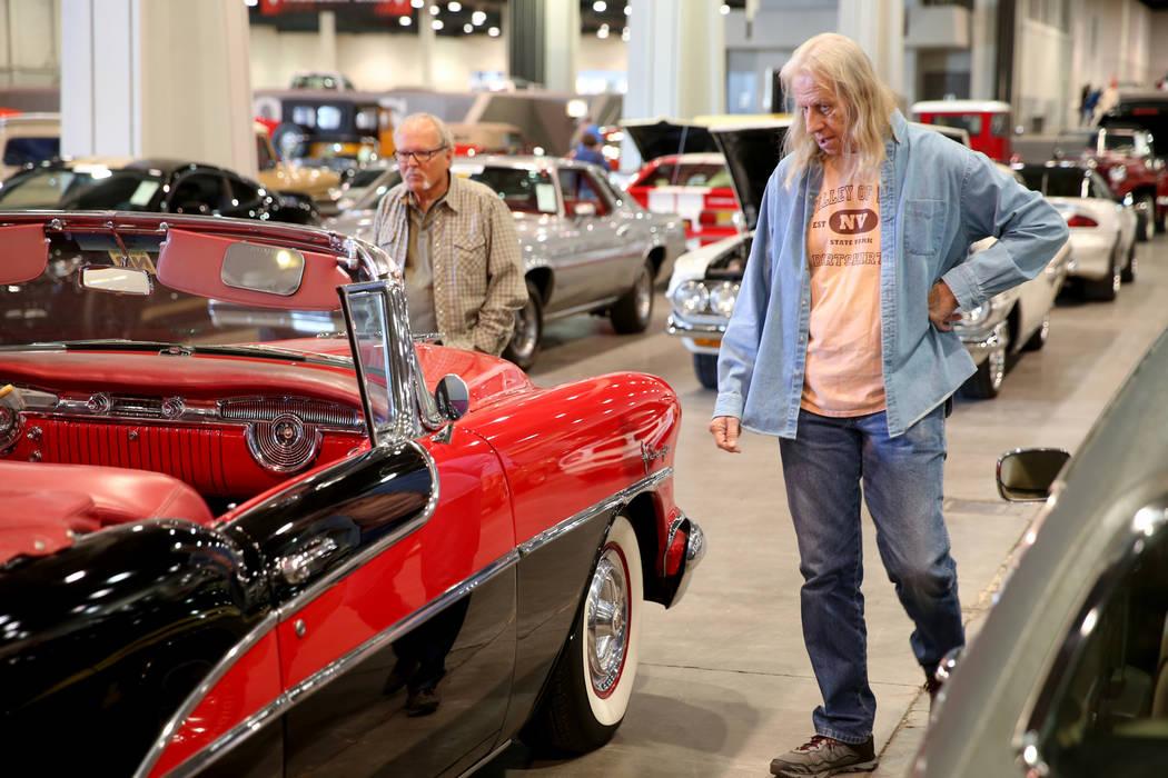 Lon Carlson, izquierda, y Roger Olsen de Las Vegas revisan autos durante la subasta de Mecum La ...