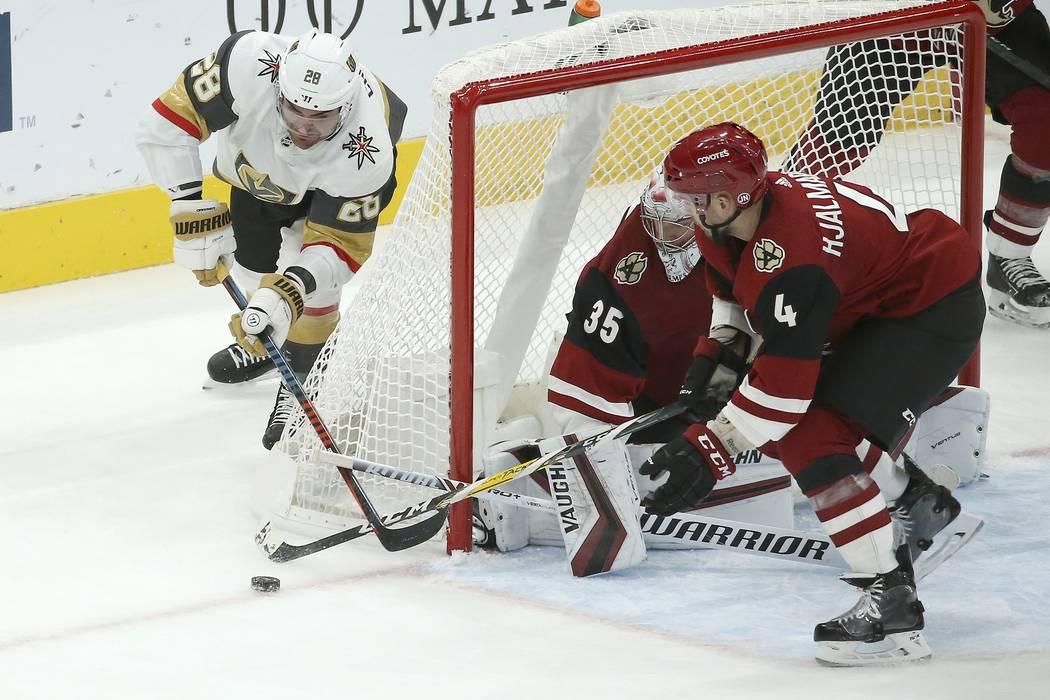 El portero de los Arizona Coyotes, Darcy Kuemper (35), recibe ayuda del defensa Niklas Hjalmars ...