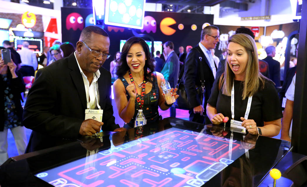 Nikki Tuazon en el stand de Gamblit Gaming, en el centro, ayuda a Vernon Finch, miembro de la c ...