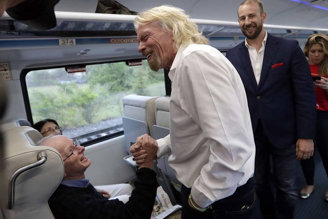 Richard Branson, del Virgin Group (al centro), saluda a un pasajero mientras viaja en un tren B ...