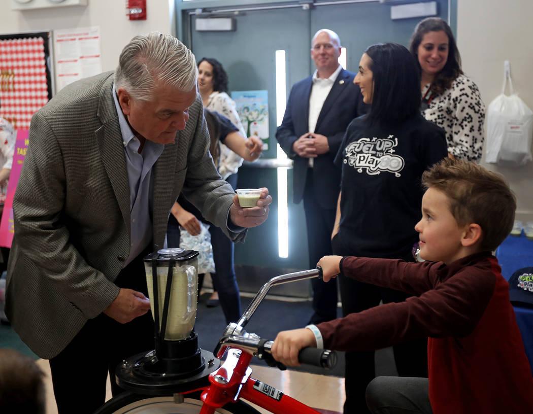 El gobernador Steve Sisolak habla con Blake Tary, de seis años, mientras pedalea una bicicleta ...
