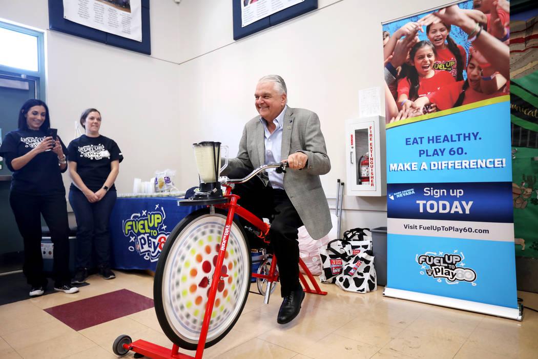 El gobernador Steve Sisolak pedalea una bicicleta que alimenta una licuadora para hacer un bati ...
