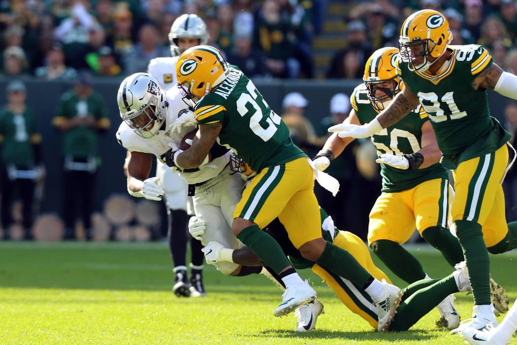 El esquinero de los Green Bay Packers, Jaire Alexander (23), derriba al corredor de los Oakland ...
