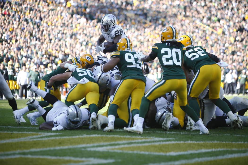 El corredor de los Oakland Raiders, Josh Jacobs (28), intenta saltar sobre los defensores de lo ...