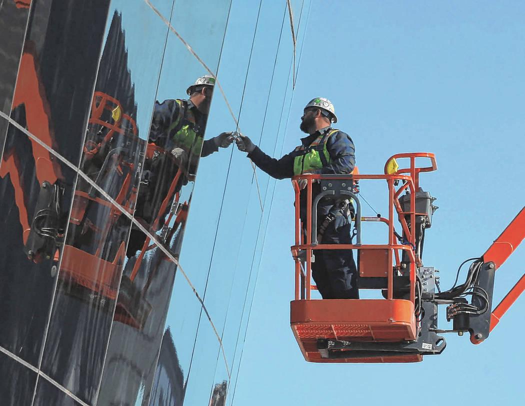 Los trabajadores revisan el vidrio instalado en el lado este del estadio Raiders Allegiant en L ...