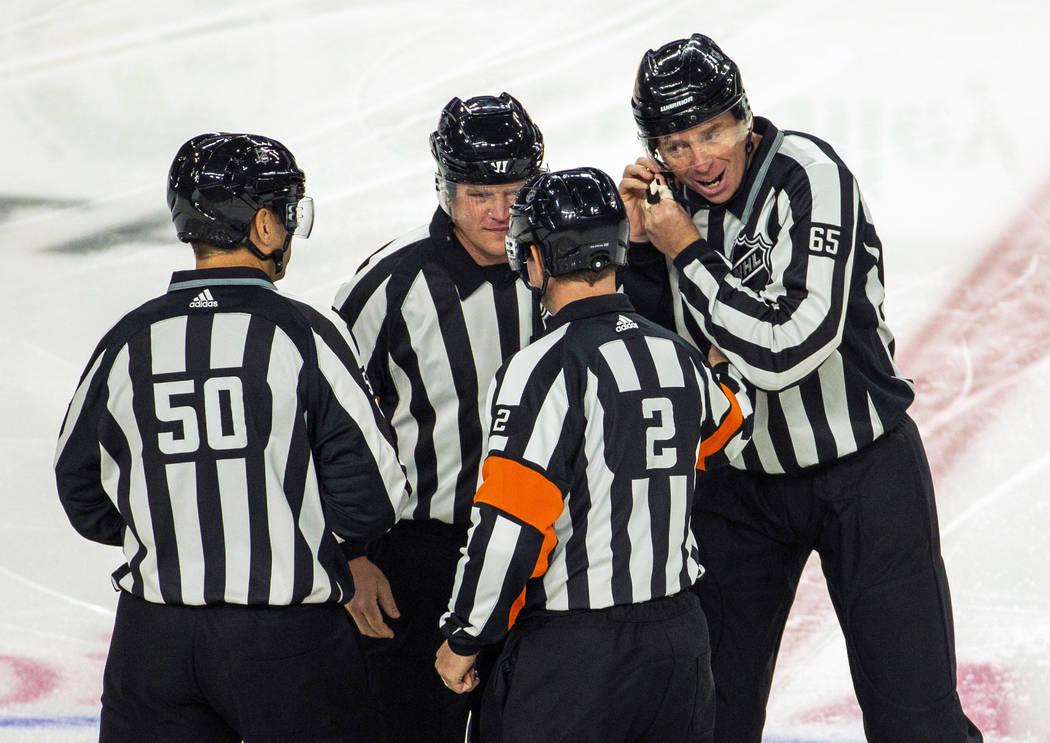 En el hielo, los árbitros se unen para dar indicaciones a los Vegas Golden Knights contra una ...
