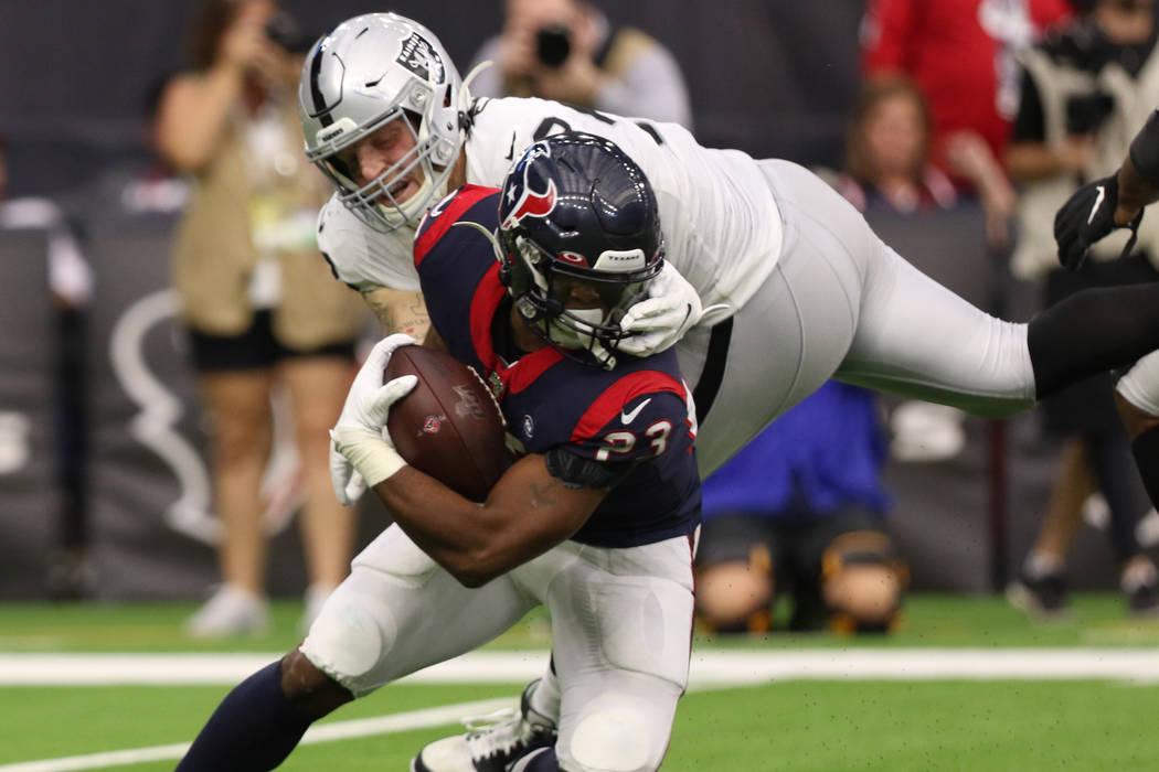 El ala defensiva de los Oakland Raiders, Maxx Crosby (98), agarra la máscara del corredor de l ...