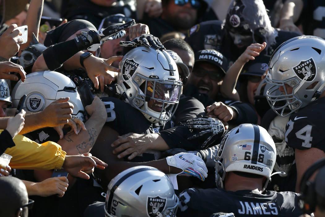 El corredor de los Oakland Raiders, Josh Jacobs, en el centro, celebra con sus compañeros y fa ...