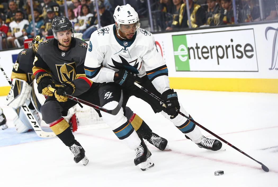 El ala izquierda de los San José Sharks, Evander Kane (9), patina con el puck bajo la presión ...