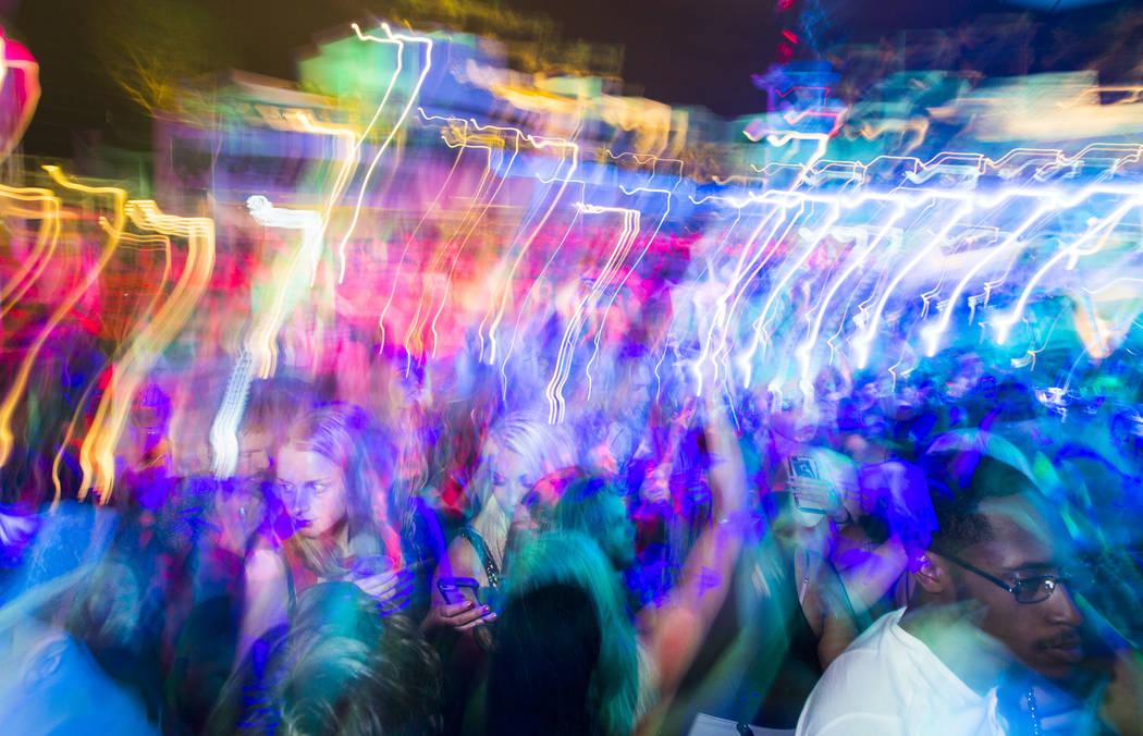 Los visitantes bailan y escuchan música mientras los artistas tocan en el escenario al aire li ...