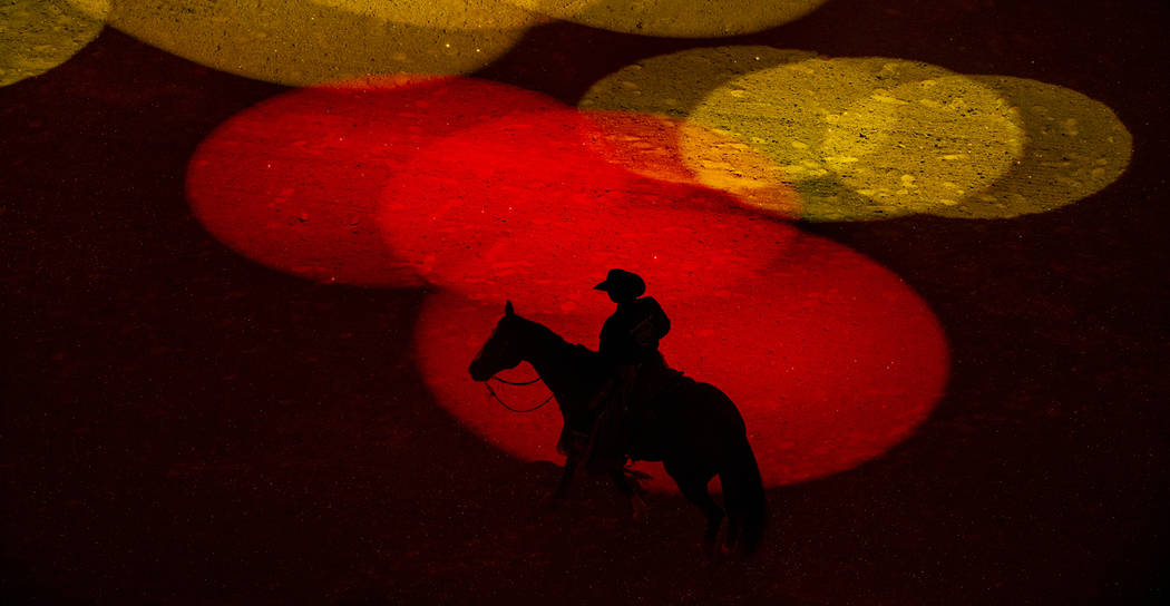 El hombre de seguridad Derrick Begay bañado en luces de colores durante la apertura de las Fin ...