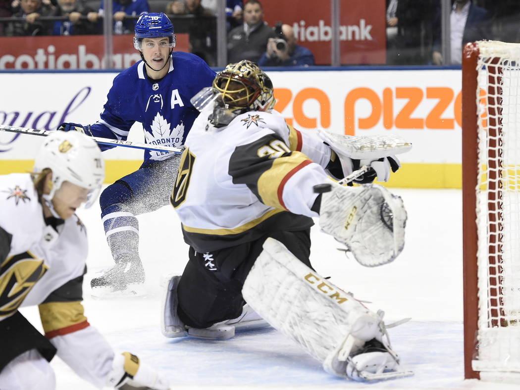 El centro de los Toronto Maple Leafs, Mitchell Marner, atrás, mira cómo un gol del centro Joh ...