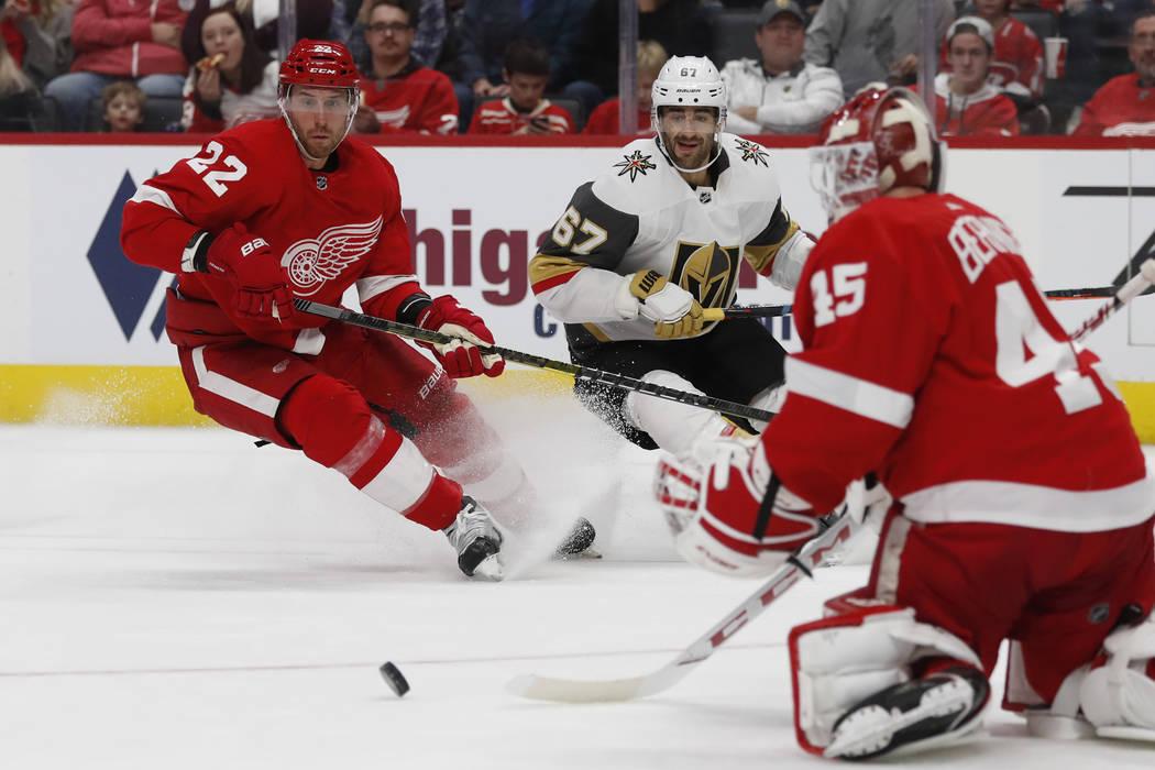 El portero de los Detroit Red Wings, Jonathan Bernier (45), desvía un tiro mientras el defensa ...