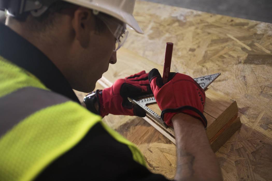 Brandon Lite toma medidas durante una clase de encuadre para HomeAid WORKS, un programa que ens ...