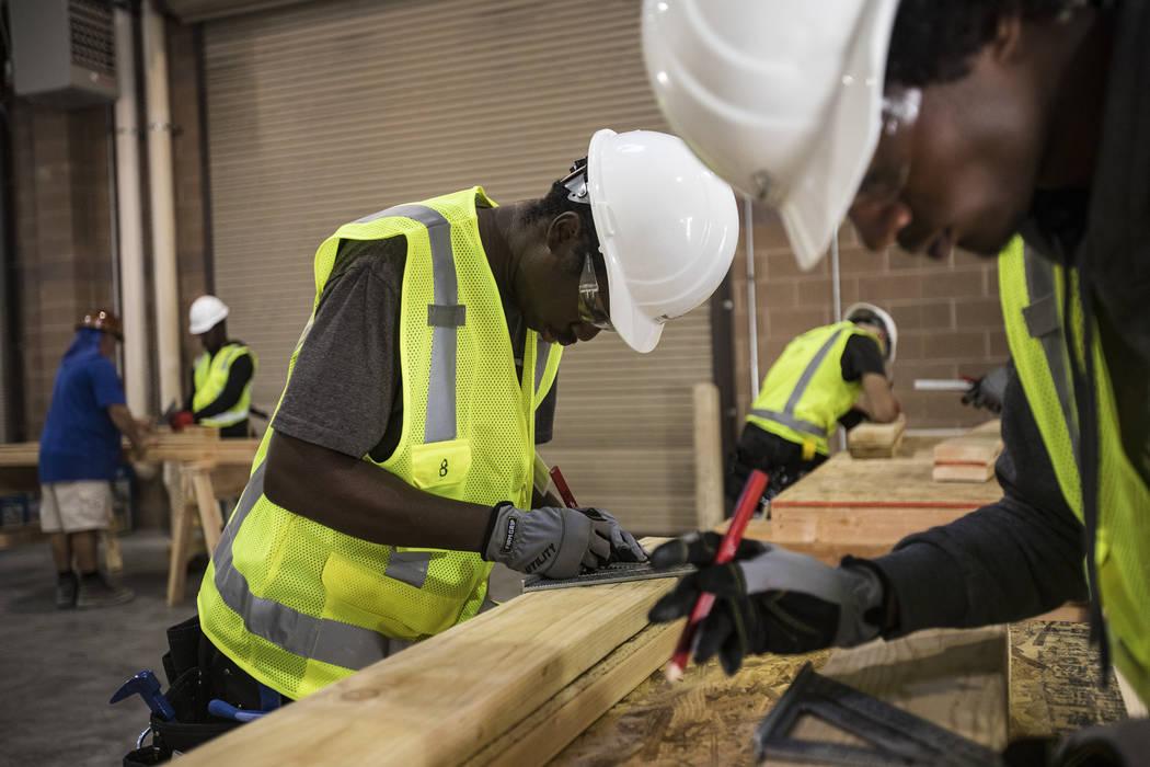 Tayvon Jenkins toma medidas durante una clase de encuadre para HomeAid WORKS, un programa que e ...
