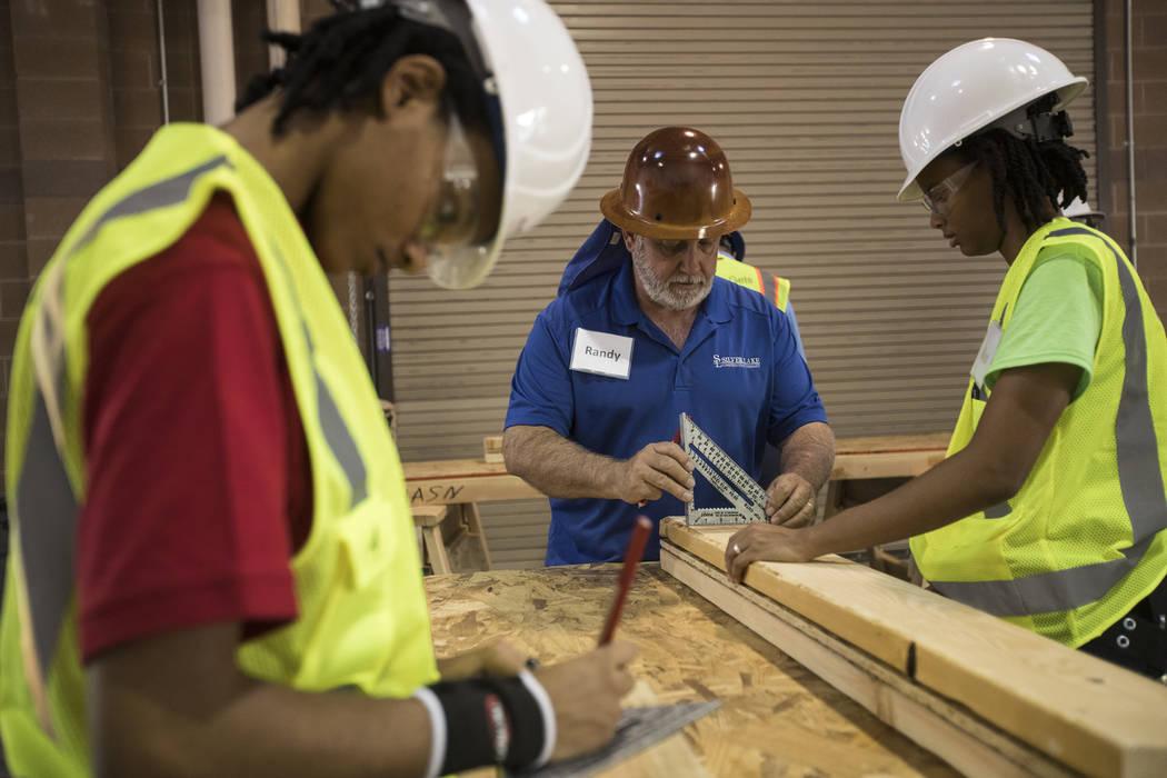 Randy Griebel, al centro, ayuda a las estudiantes y hermanas Tamira Williams, a la izquierda, y ...