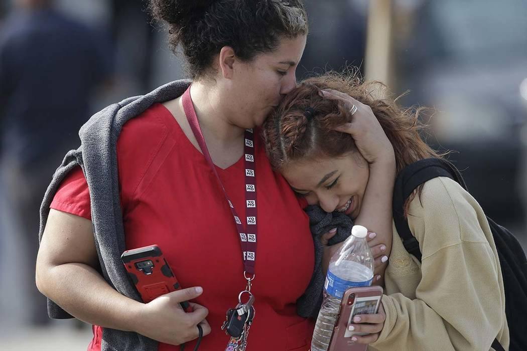 La madre Alicia León, izquierda, besa a su hija, Alejandra Cruz, de décimo grado, mientras se ...