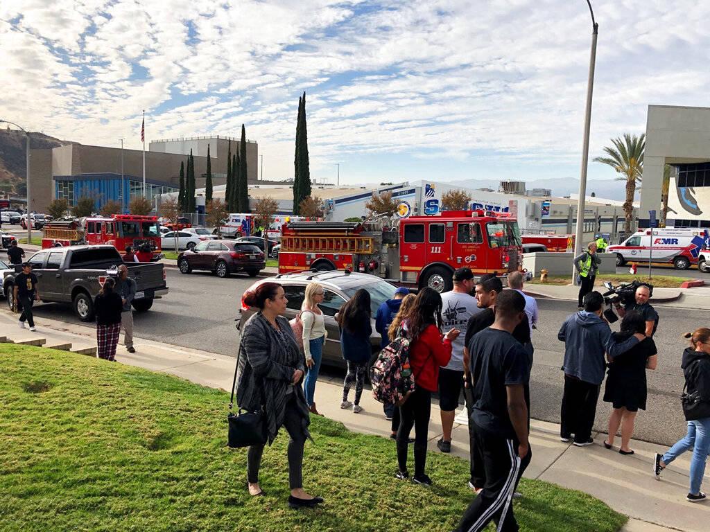 Gente espera a los estudiantes y actualizaciones afuera de la Preparatoria Saugus después de l ...