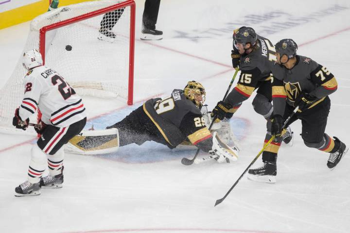 El centro de Chicago Blackhawks, Ryan Carpenter (22), mira un disparo de su compañero de equip ...