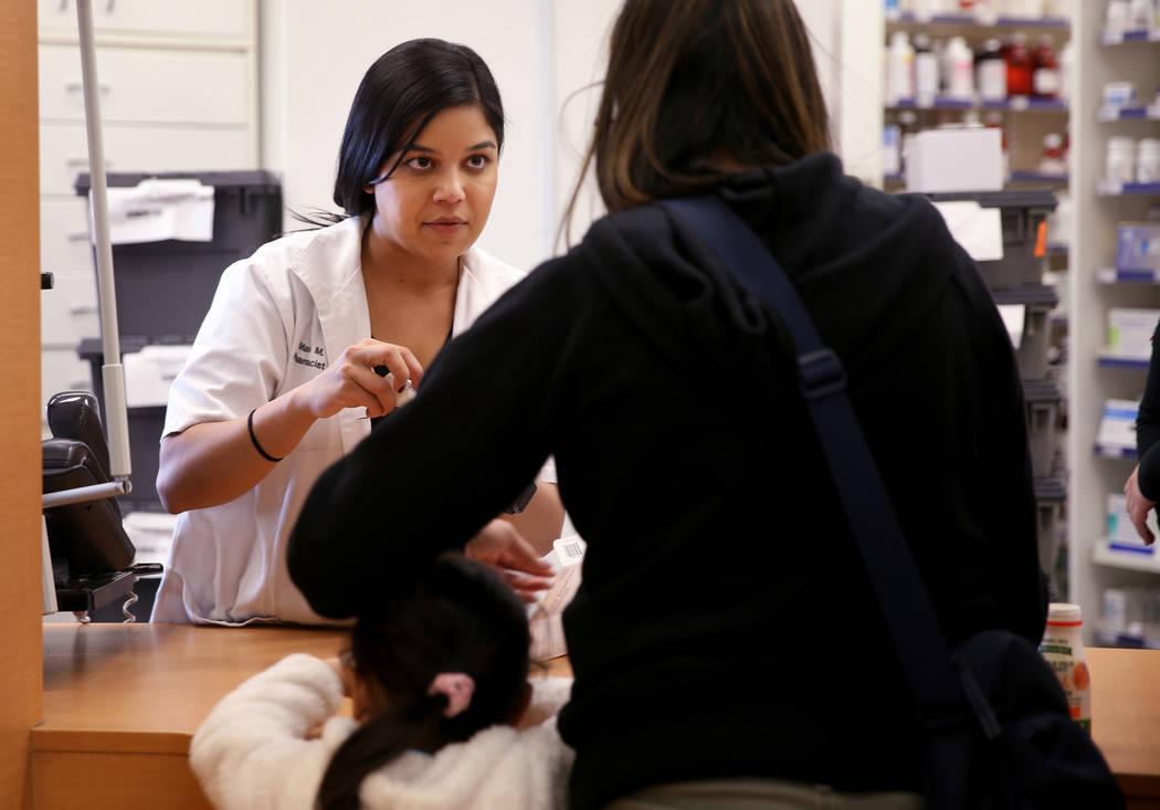 La gerente de farmacia, María Masood, atiende la receta de un cliente en la farmacia Walgreens ...