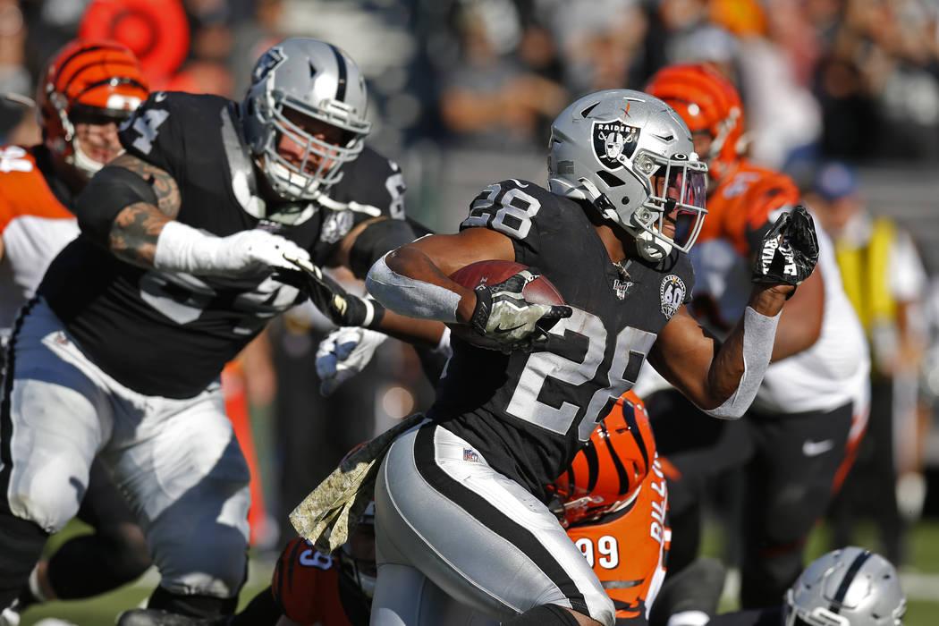El corredor de los Oakland Raiders, Josh Jacobs, carga la pelota durante la primera mitad de un ...