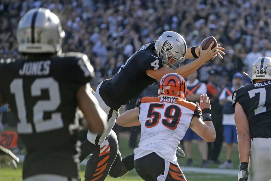 El mariscal de campo de los Oakland Raiders, Derek Carr (4), salta con el balón por encima de ...
