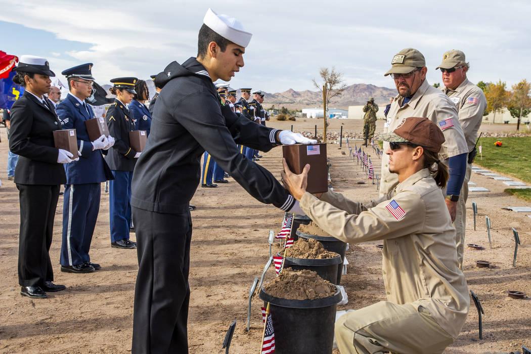 El marinero Alex Ramírez le presenta una urna a Brandon Hall para enterrarla en el Southern Ne ...