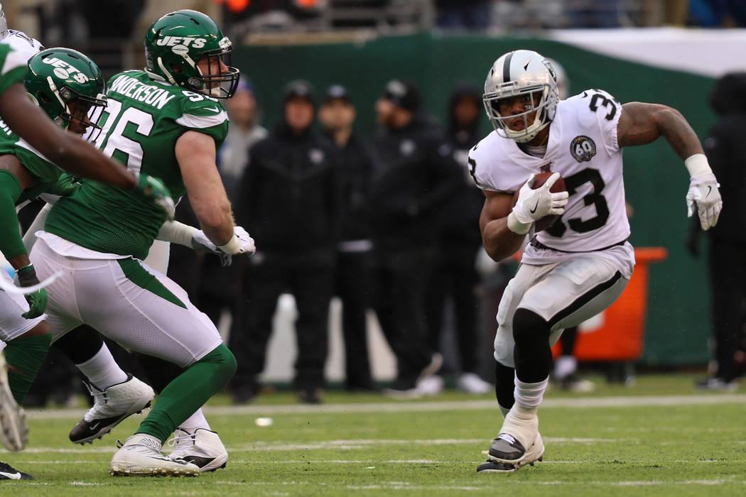 El corredor de los Oakland Raiders, DeAndre Washington (33), corre con el balón mientras el ex ...