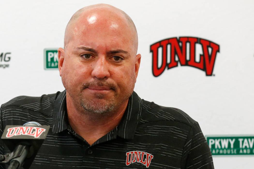 El entrenador principal de fútbol de la UNLV, Tony Sánchez, escucha la pregunta de un reporte ...