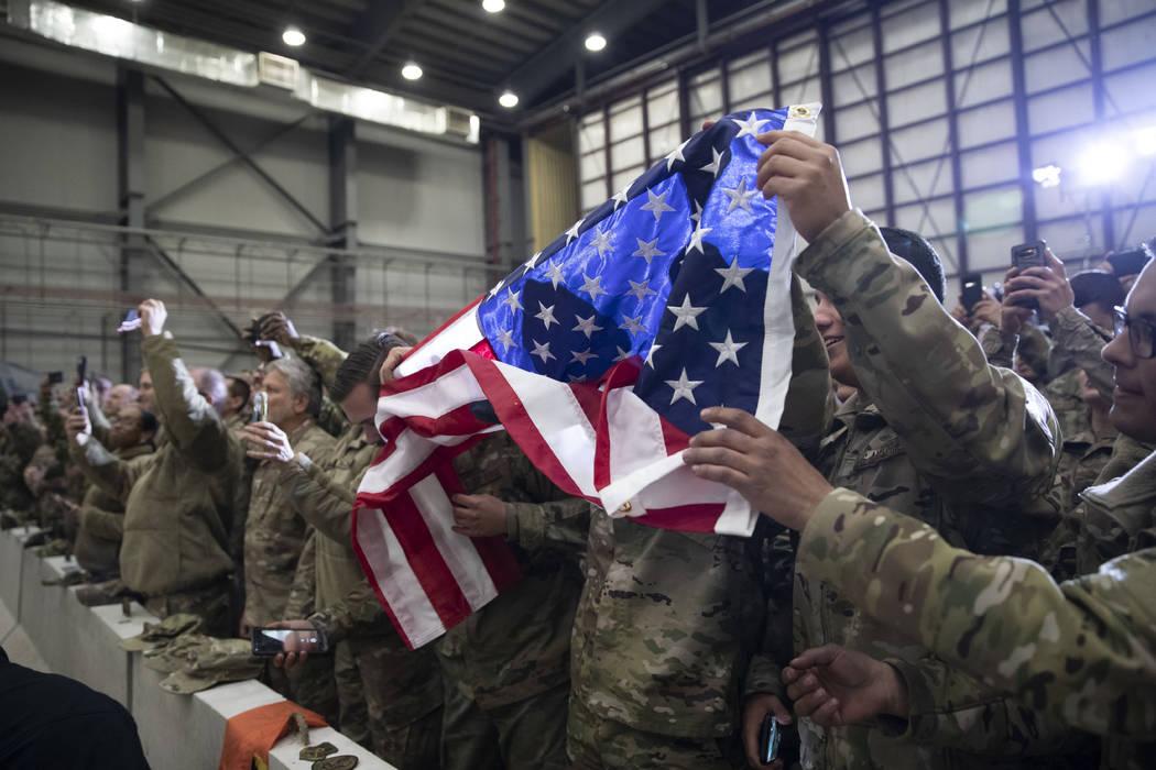 Miembros del ejército despliegan una bandera estadounidense mientras el presidente Donald Trum ...