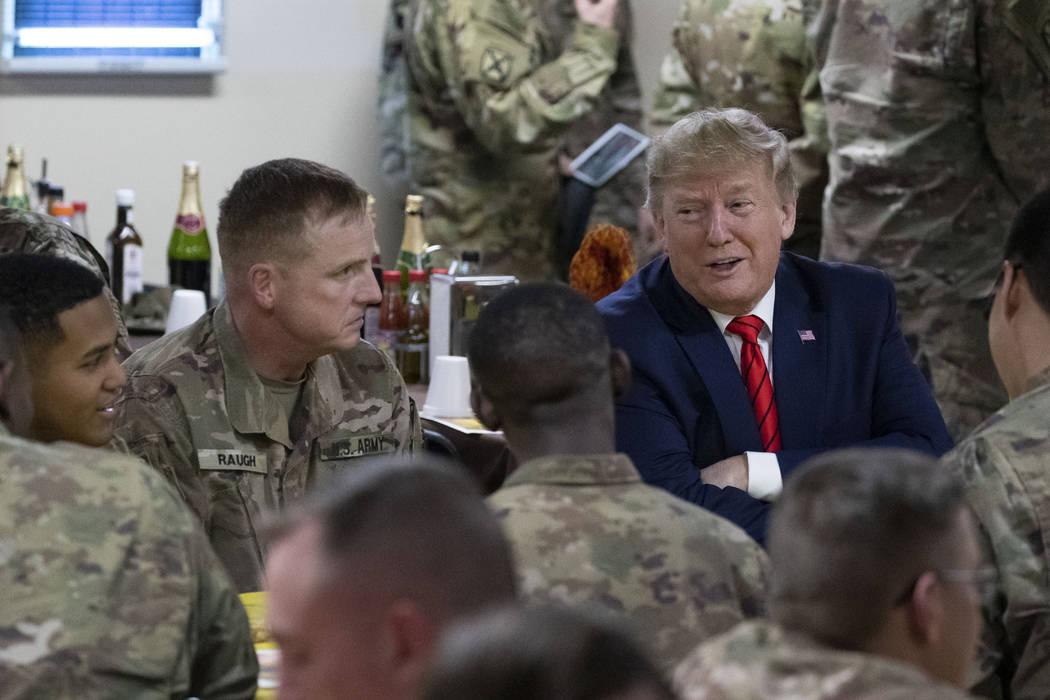 El presidente Donald Trump habla con miembros del Ejército durante una visita sorpresa del Dí ...