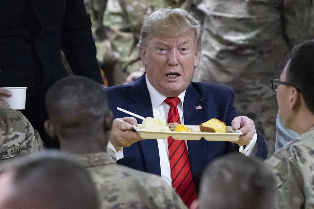 El presidente Donald Trump sostiene una bandeja de la cena de Acción de Gracias durante una vi ...