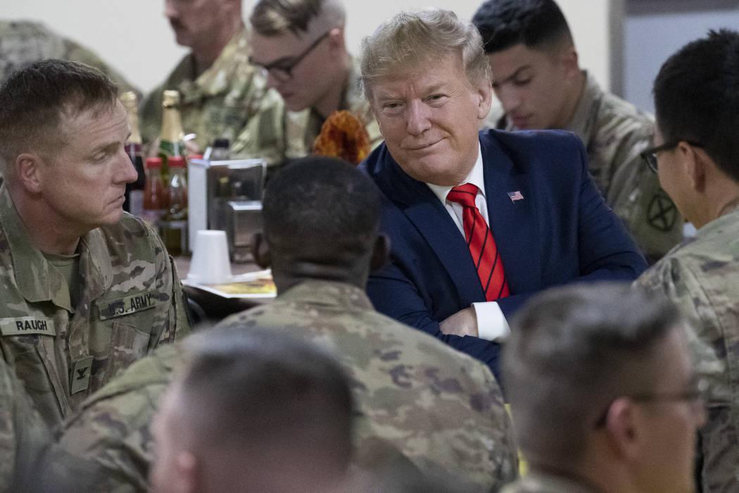 El presidente Donald Trump sonríe mientras está sentado con las tropas durante una visita sor ...