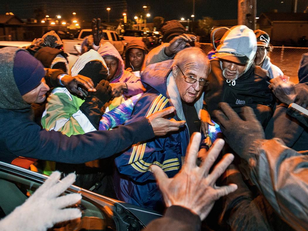 Una multitud se reúne alrededor del Padre John McShane mientras regala pases de autobús y otr ...