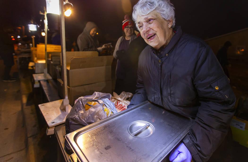 La voluntaria Christine Ruland ayuda a servir una cena caliente a los necesitados reunidos para ...