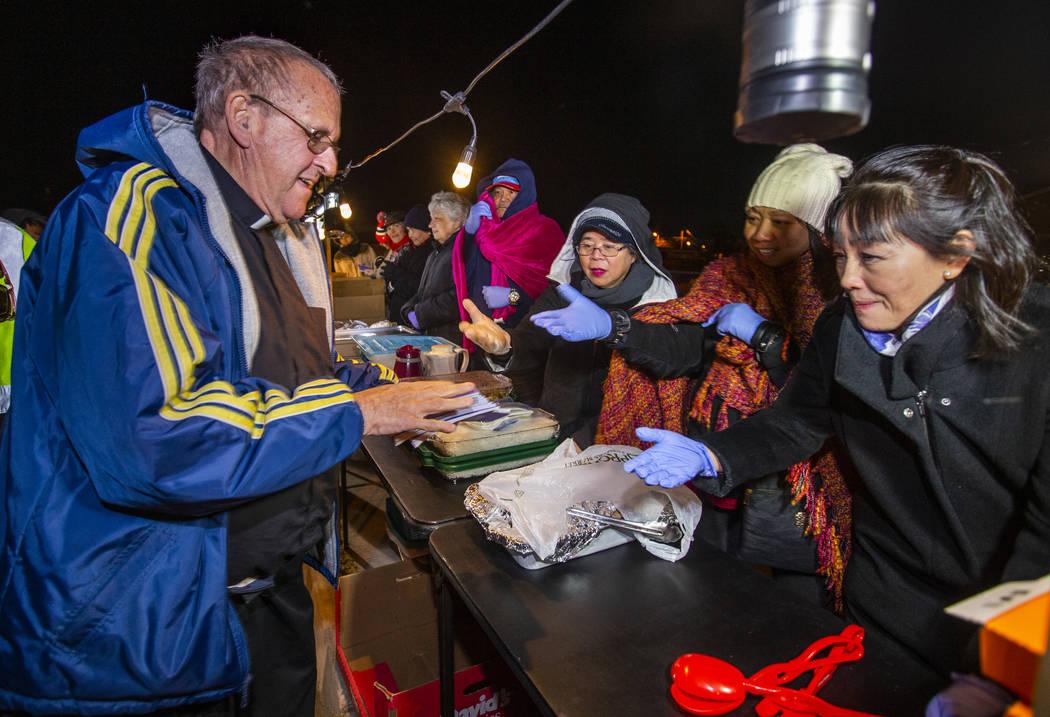 El Padre John McShane, a la izquierda, reparte libros de oraciones a algunos de los voluntarios ...