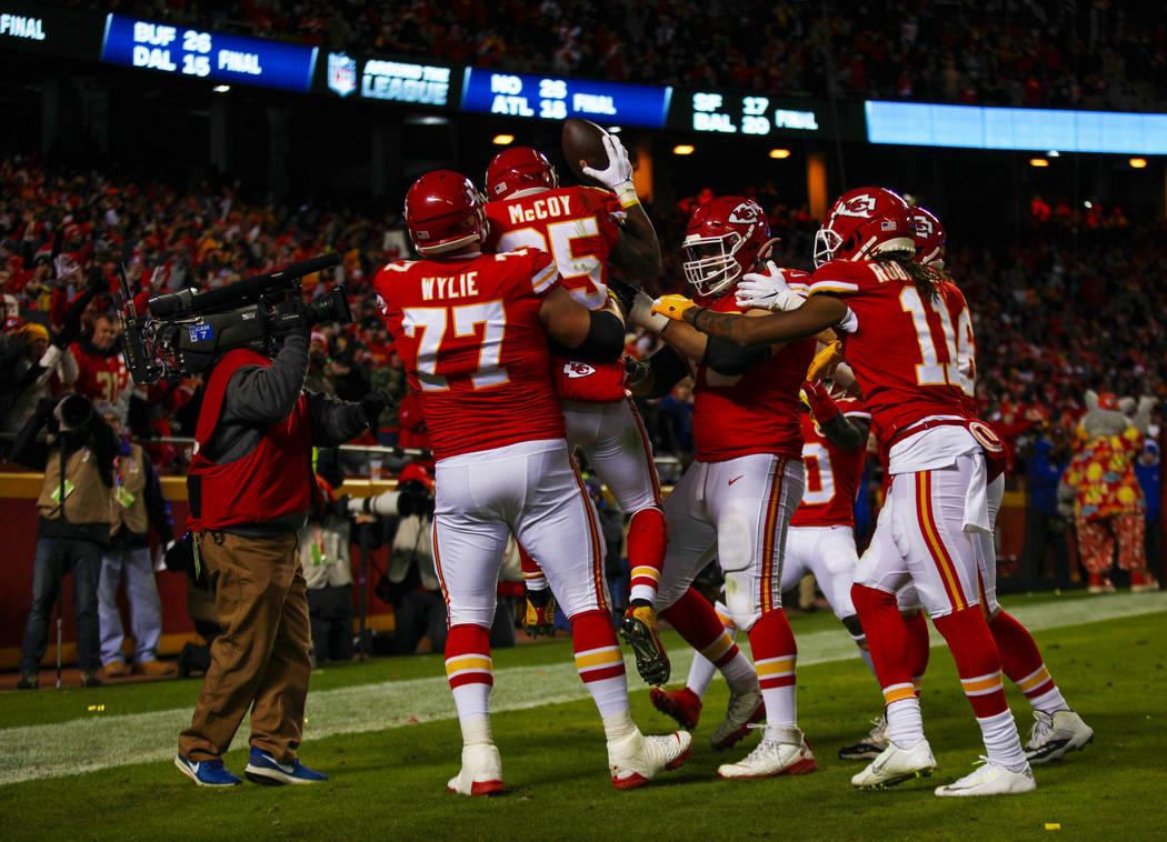 El corredor de los Kansas City Chiefs, LeSean McCoy (25), es levantado por el guardia ofensivo ...