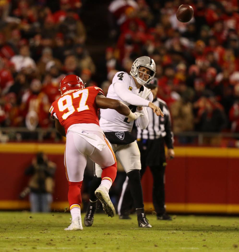 El mariscal de campo de los Oakland Raiders, Derek Carr (4), lanza el balón mientras es presio ...