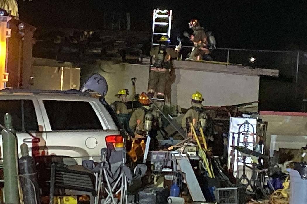 Los equipos de bomberos trabajan en un incendio en una casa de huéspedes cerca de las carreter ...