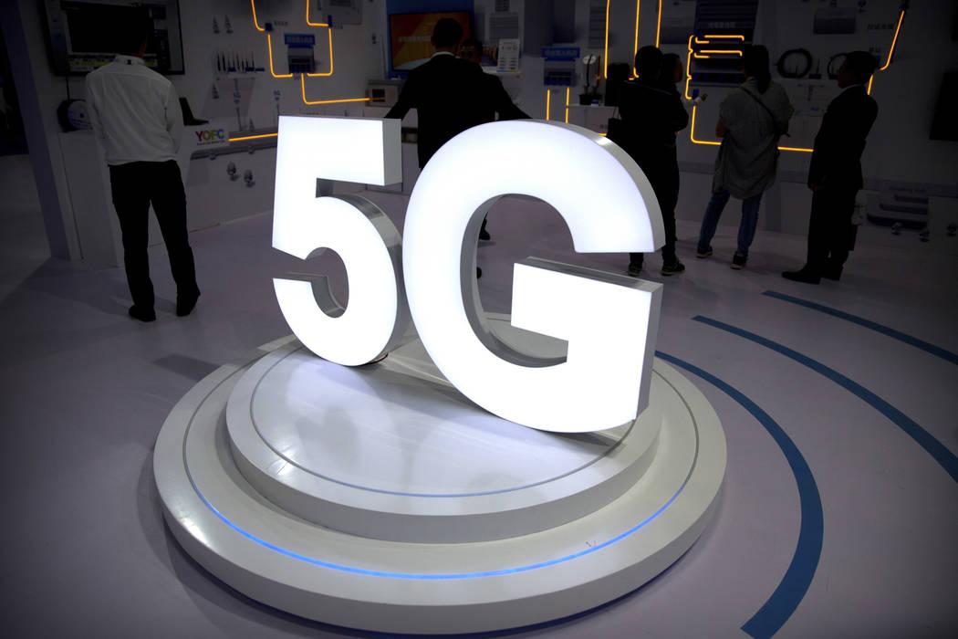 Visitantes cerca de un logotipo 5G en una exposición de PT Expo en Pekín en 2018. (Foto AP/Ma ...