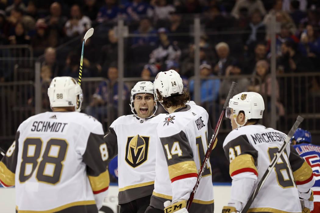 El ala derecha de los Golden Knights de Las Vegas, Alex Tuch, segundo desde la izquierda, reacc ...