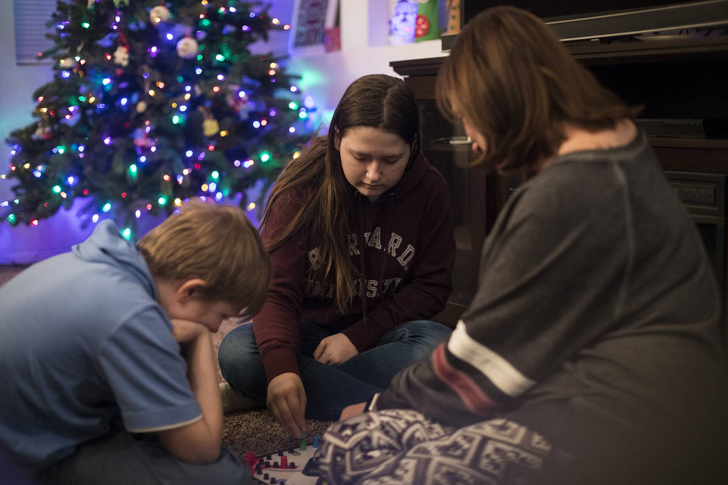 Rebecca Cabral, 14, center, plays a board game with her brother Joseph Cabral, 12, left, and th ...