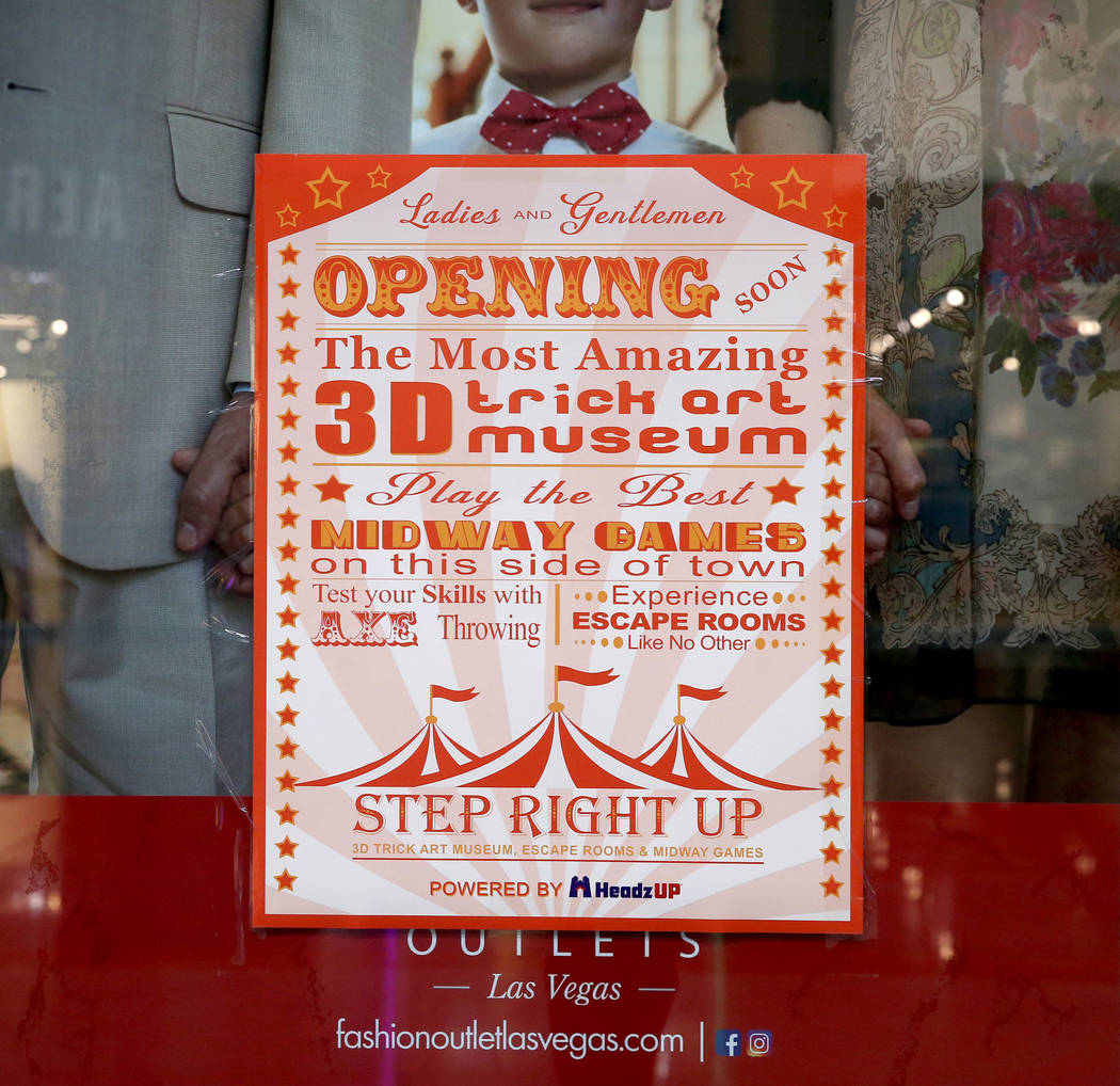 Un cartel de una nueva atracción, Step Right Up, sobre un anuncio en Fashion Outlets of Las Ve ...
